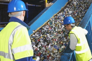 Two workers monitoring conveyor belt of recycled cans, back view