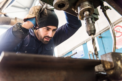 Worker at milling machine in workshop.