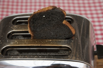 Slice of burnt toast in a toaster machine