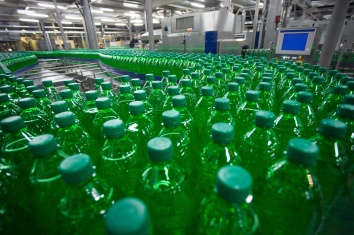 Green plastic bottles on the conveyor belt at the plant