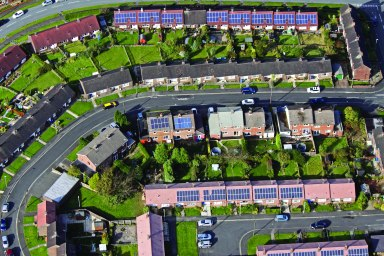 aerial view of modern and older houses and bungalows with solar panels on the roof