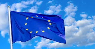 Flag of the European Union waving in the wind on flagpole against the sky with clouds, banner